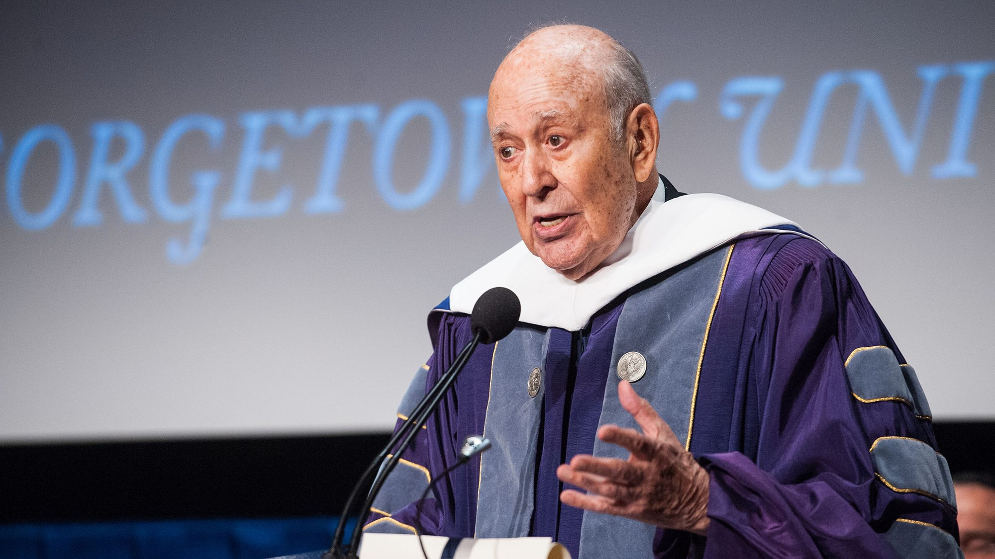 Carl Reiner at a podium wearing academic robs with a screen behind him reading Georgetown University