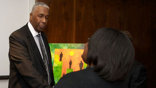 John Thompson Jr. speaks with a woman at a local Boys & Girls Club.