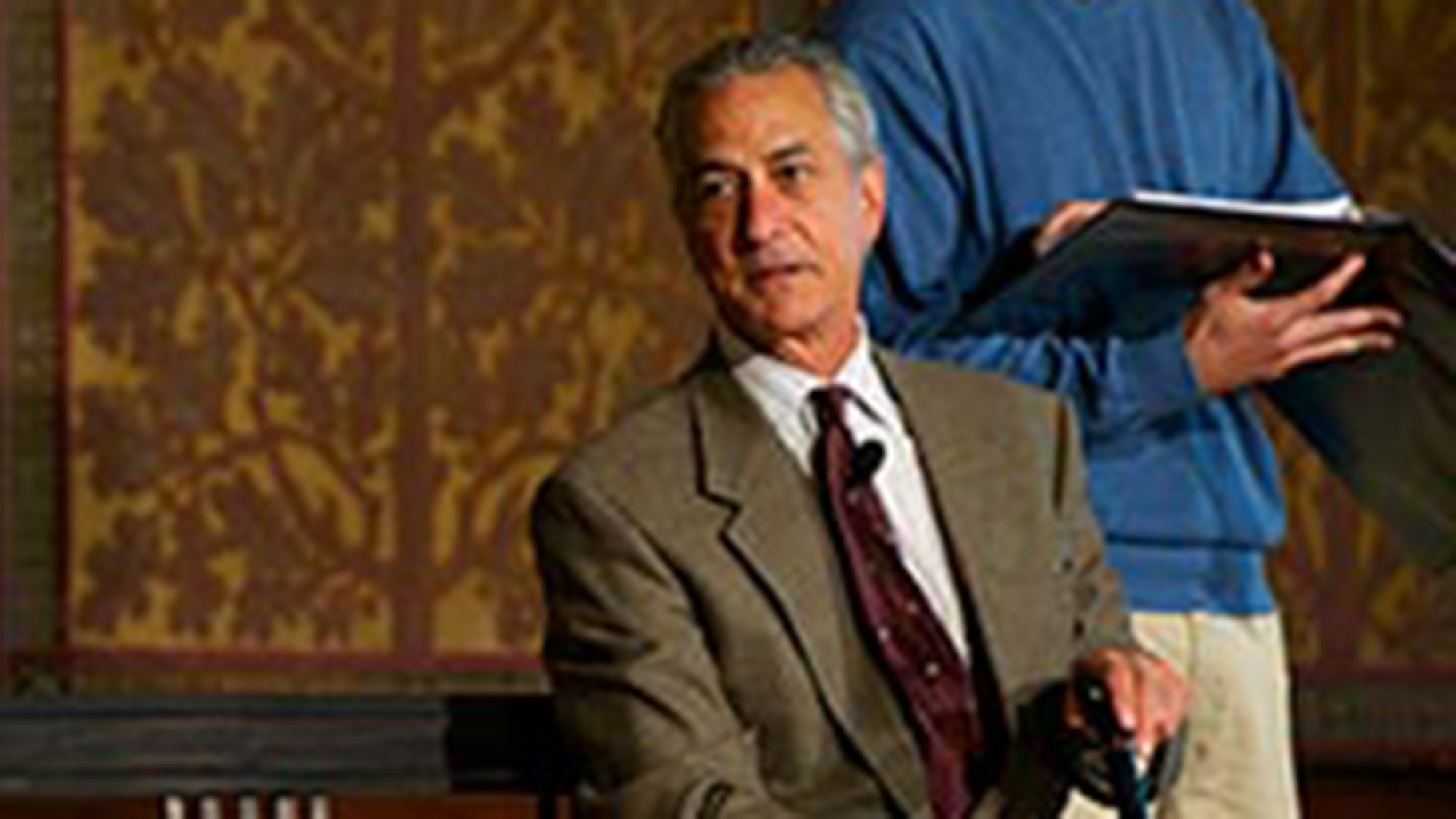 David Strathairn acting as Jan Karski on stage sitting on a bench with student actor behind him