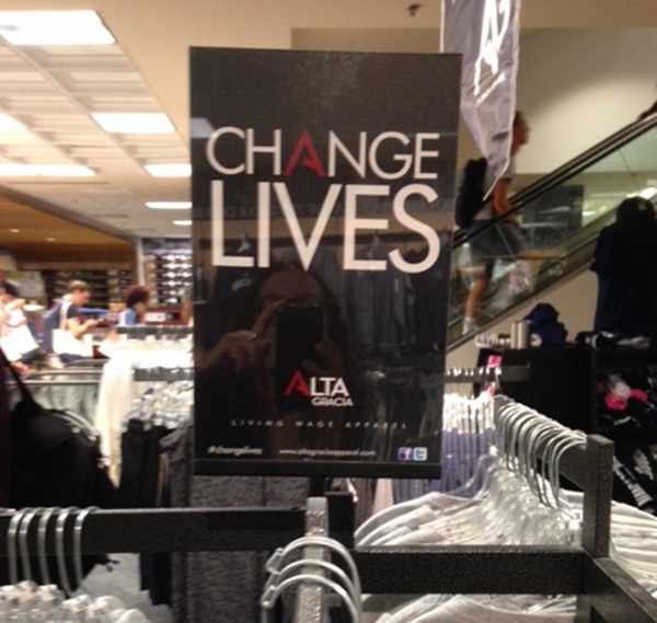 A sign that says Change Lives Alta Gracia with rows of apparel in the Georgetown bookstore