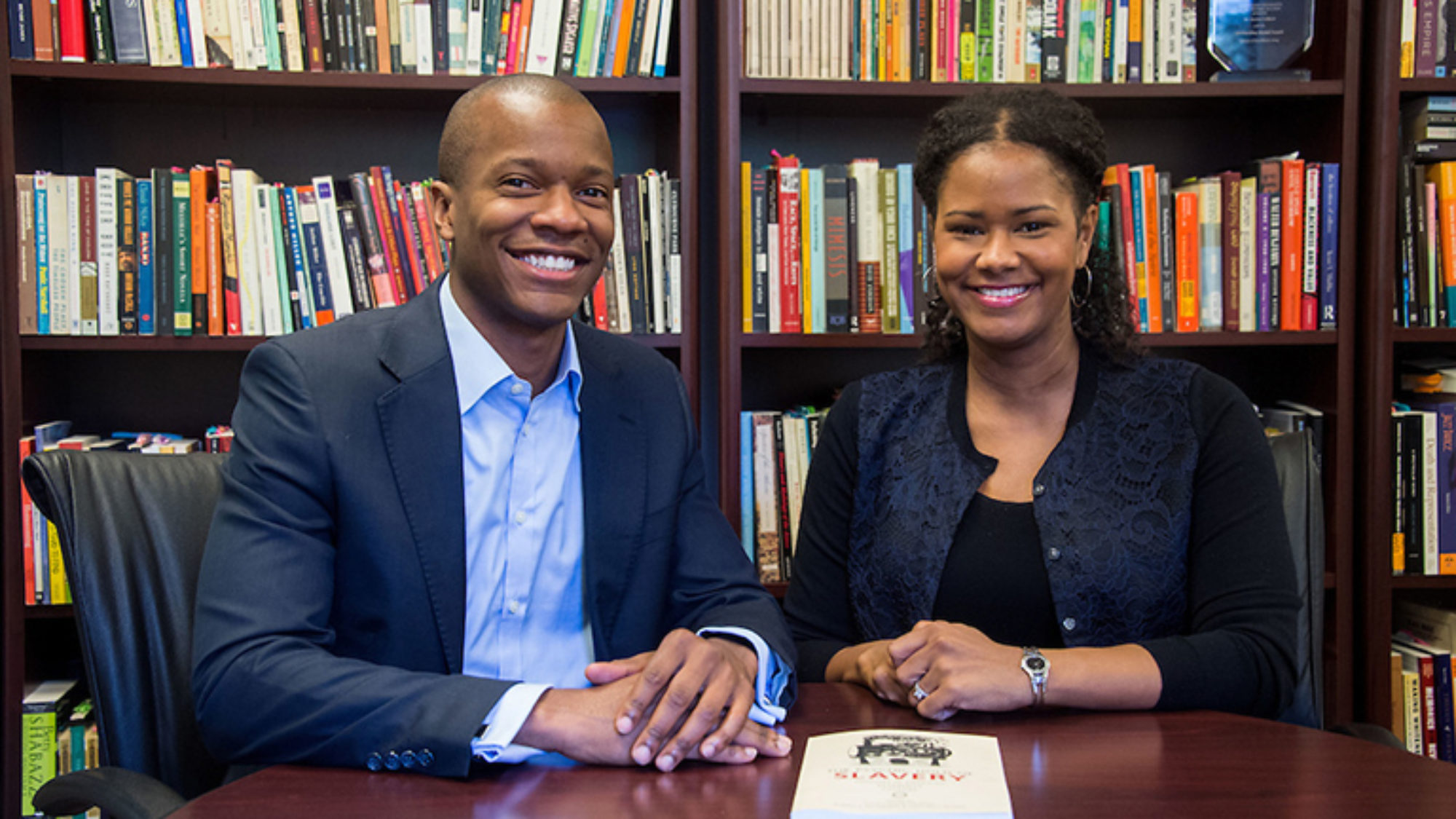 Robert Patterson and Soyica Colbert sit at a table with their book and a bookcase behind them.