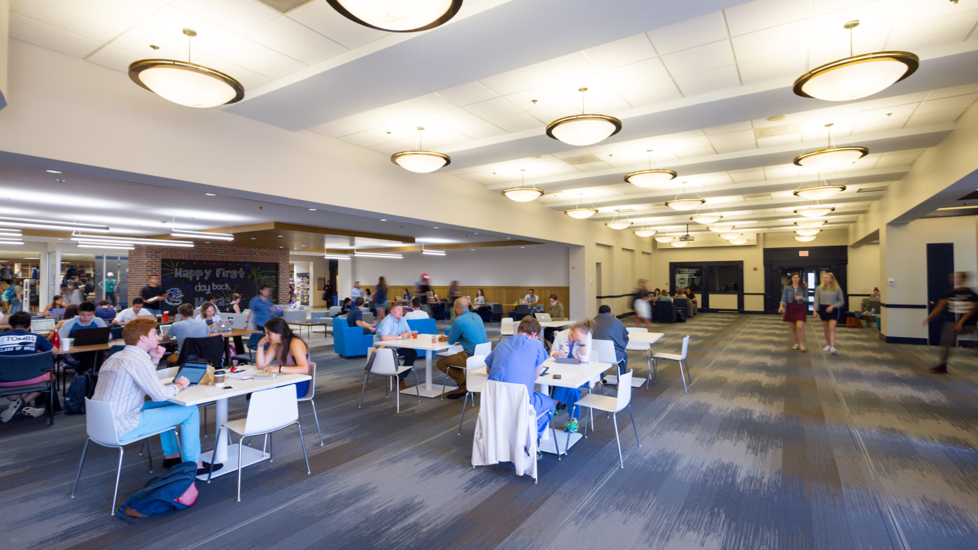 Students are pictured studying in the Leavey Center at different tables.