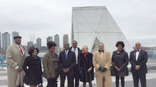 Descendants and other members of the Georgetown community stand before a sculpture at the United Nations in New York