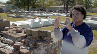 Jessica Tilson gesturing with hands in a cemetery where her ancestors are buried