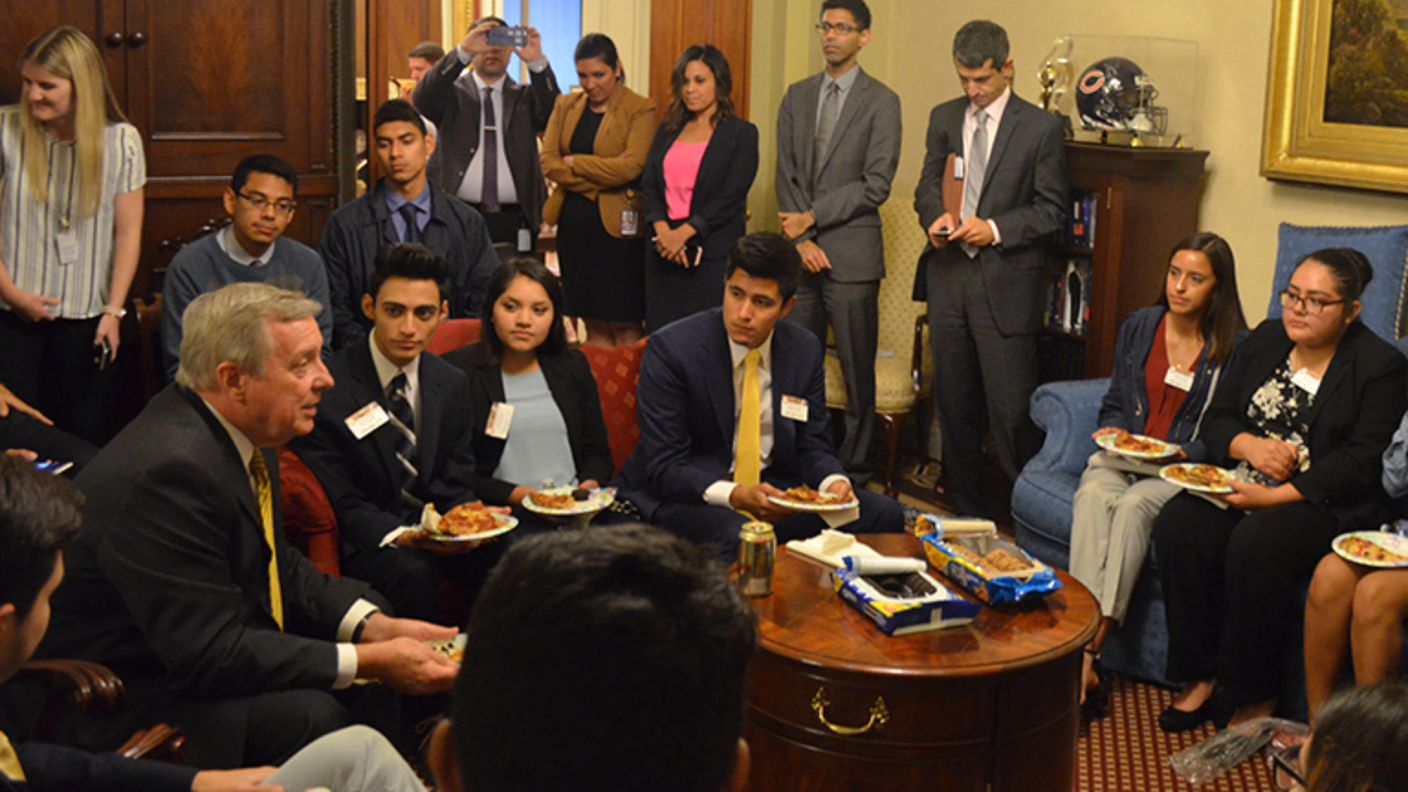 Sen. Richard Durbin sitting in his office on Capitol Hill surrounded by Georgetown undocumented students and others