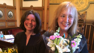 Mary Esselman and Elizabeth Velez with a bouquet of flowers.