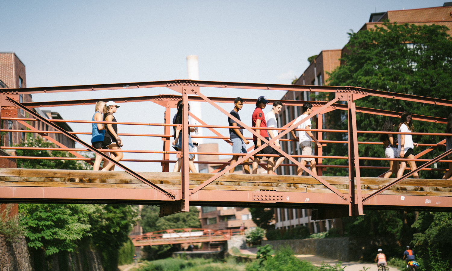 People are seen crossing a bridge over the Georgetown canal.