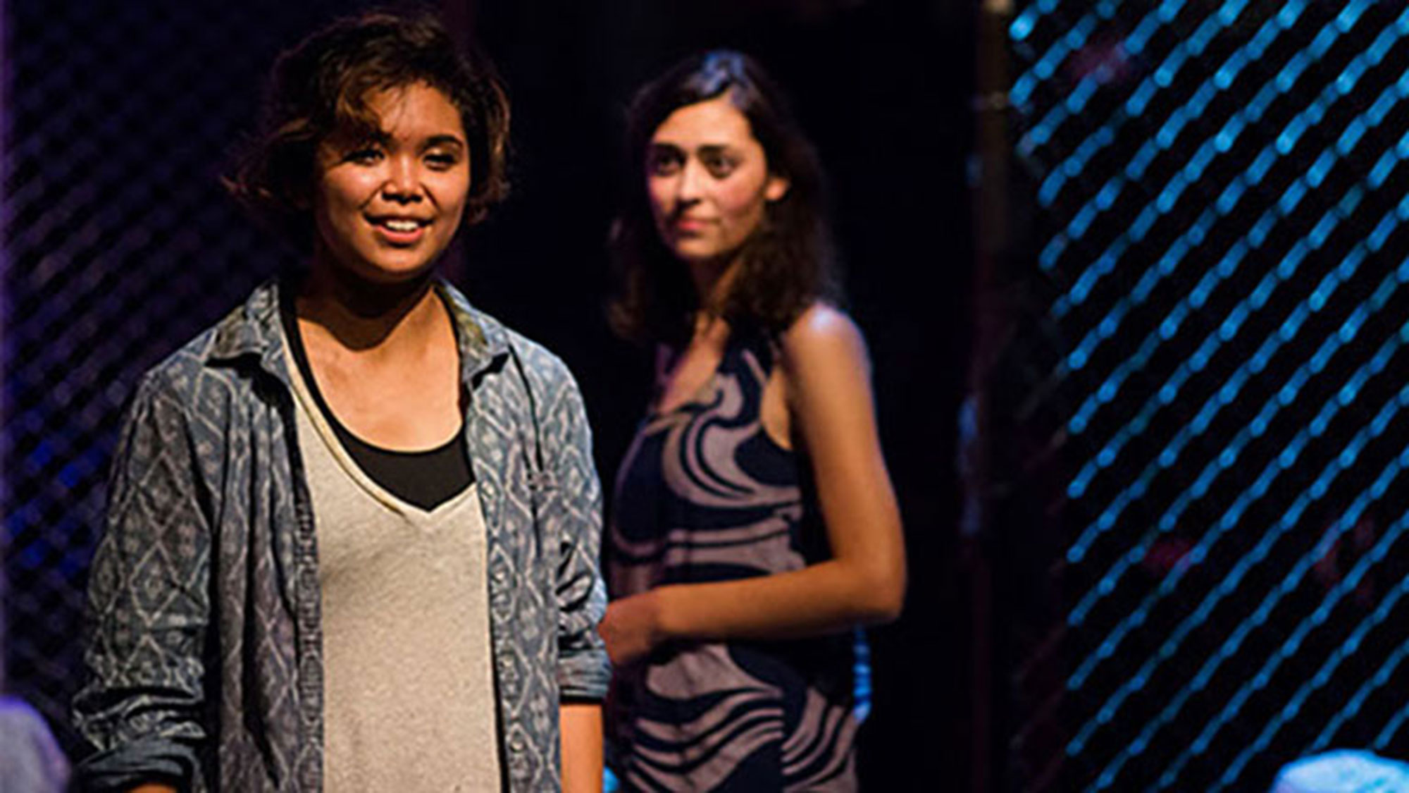 Cristina Ibarra speaks on a theater stage with another actress behind her.
