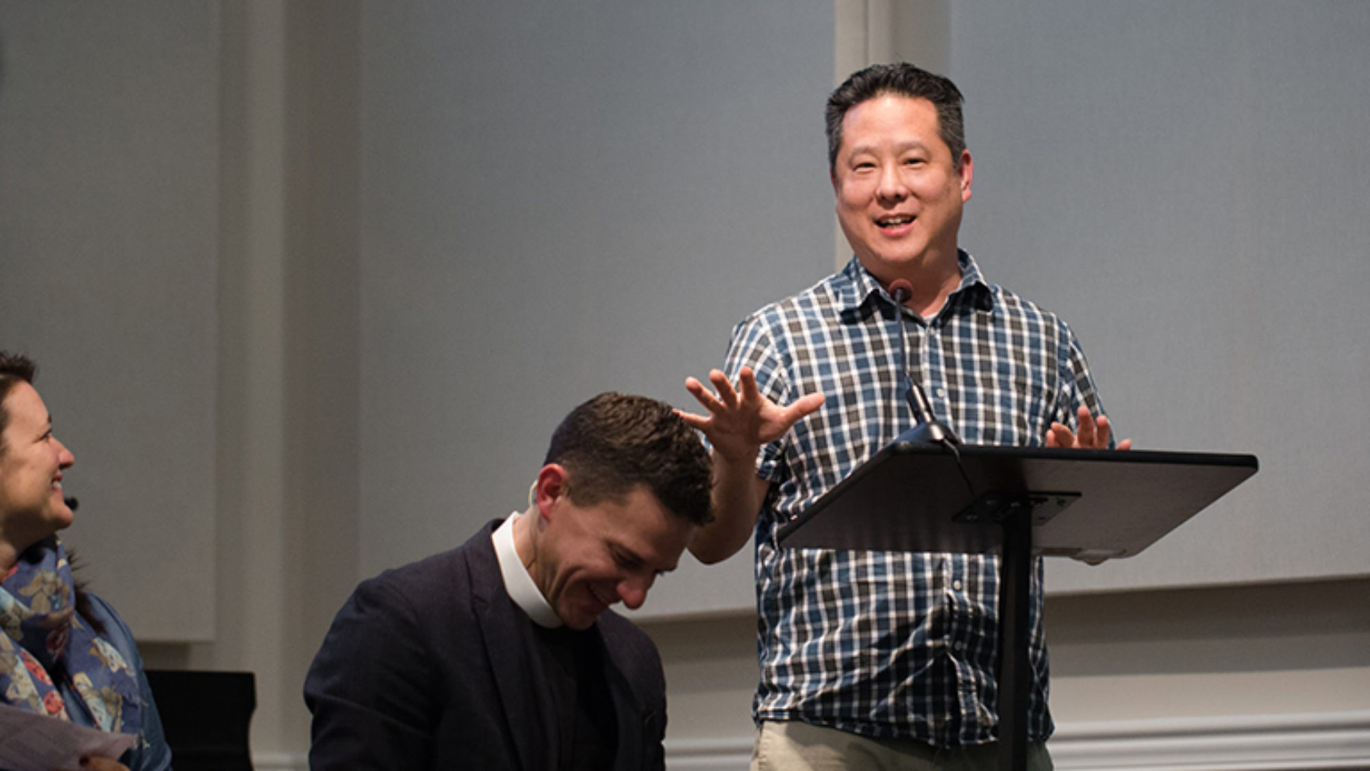 Steve Park at a podium with two people sitting and laughing.
