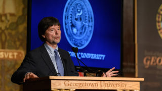 Ken Burns speaking at podium with Georgetown University banner and seal