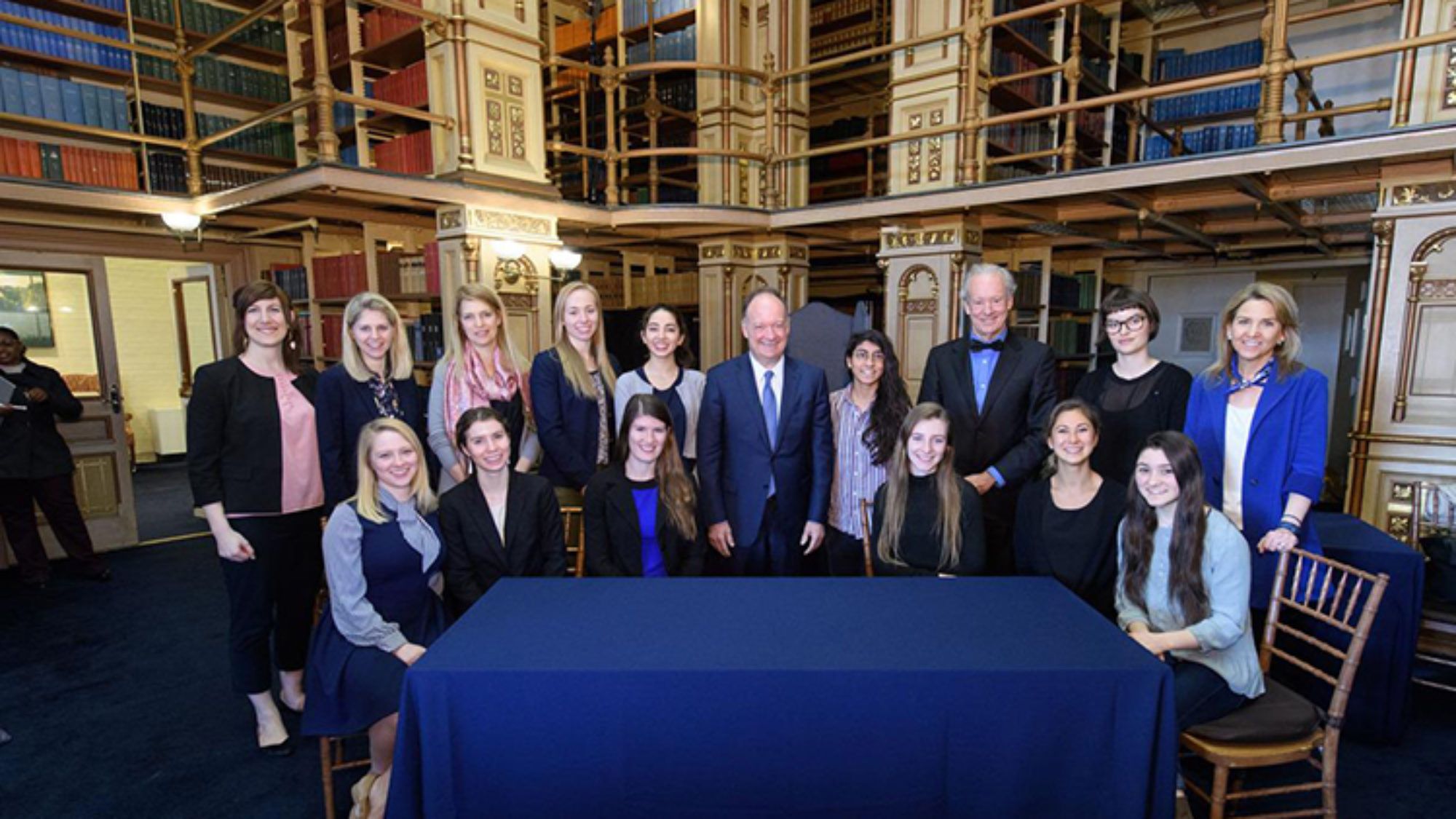 Bill McDonough and John J. DeGioia stand around a table with students and administrators