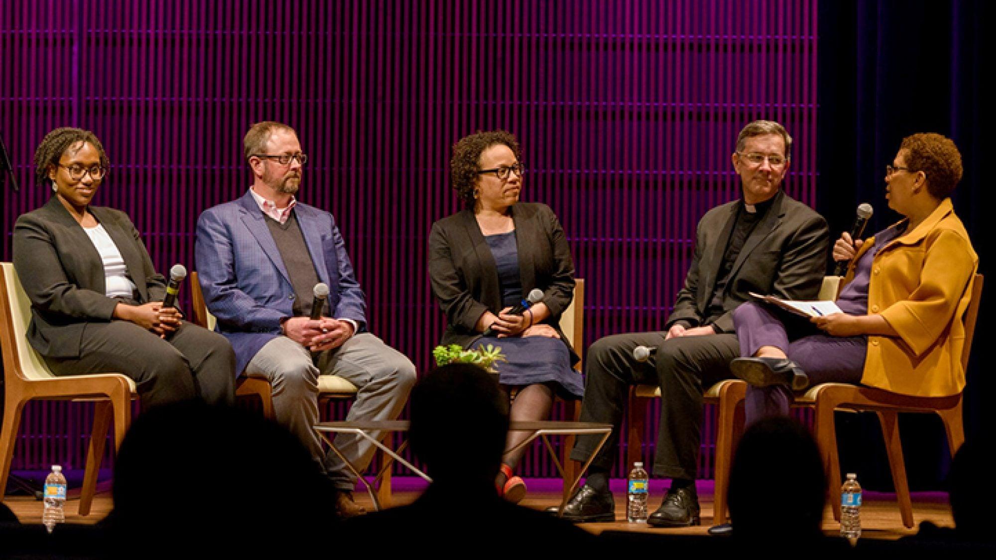 Panelists sit on a stage