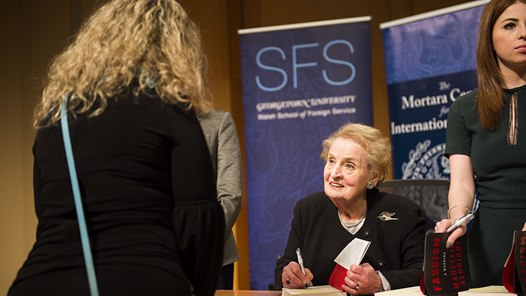Madeleine Albright signs a book while a student looks on