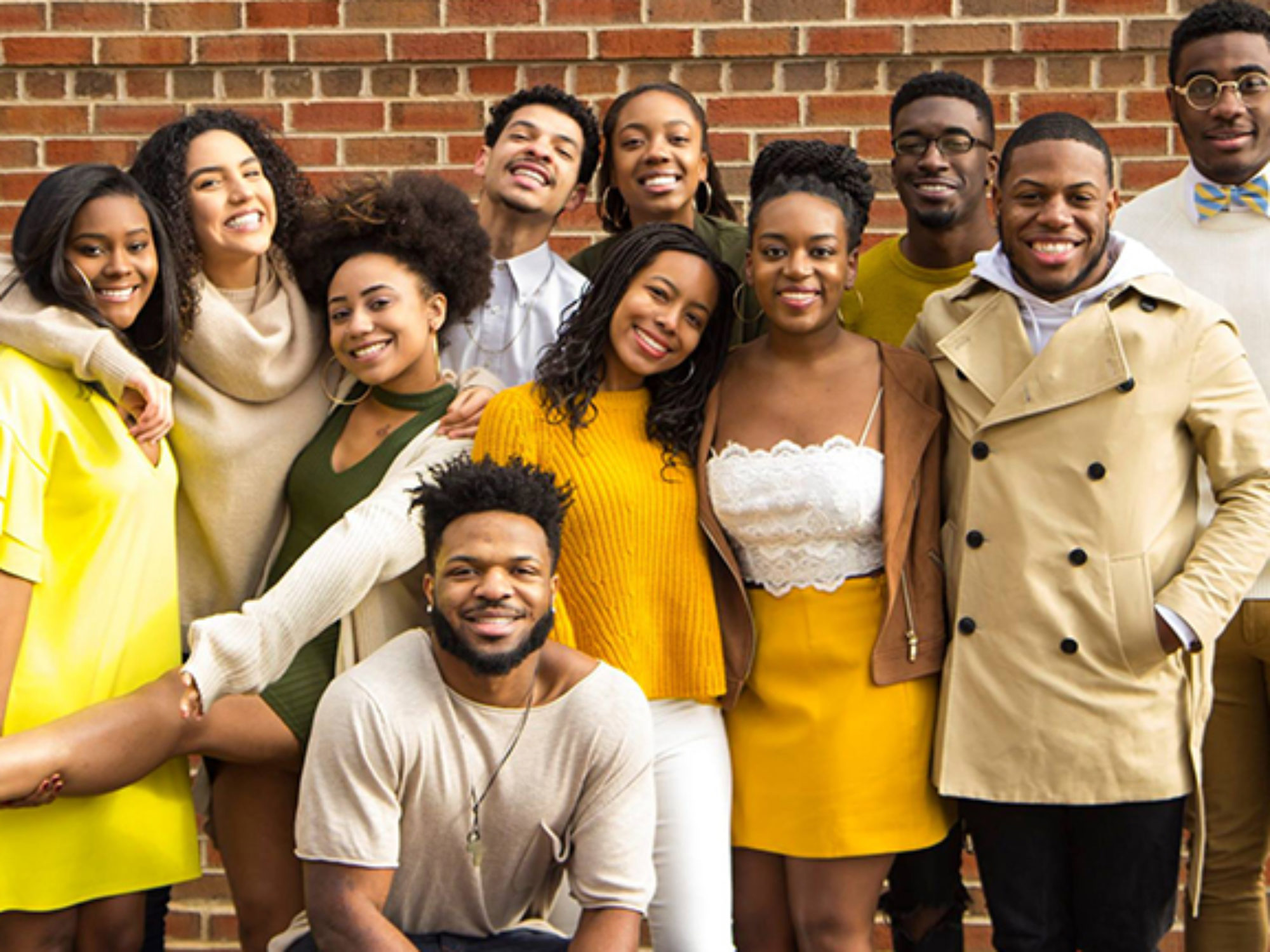 Members of Black Student Alliance smiling in front of a brick wall.
