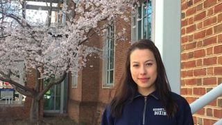 Hana Burkly outside in front of a building and a cherry tree