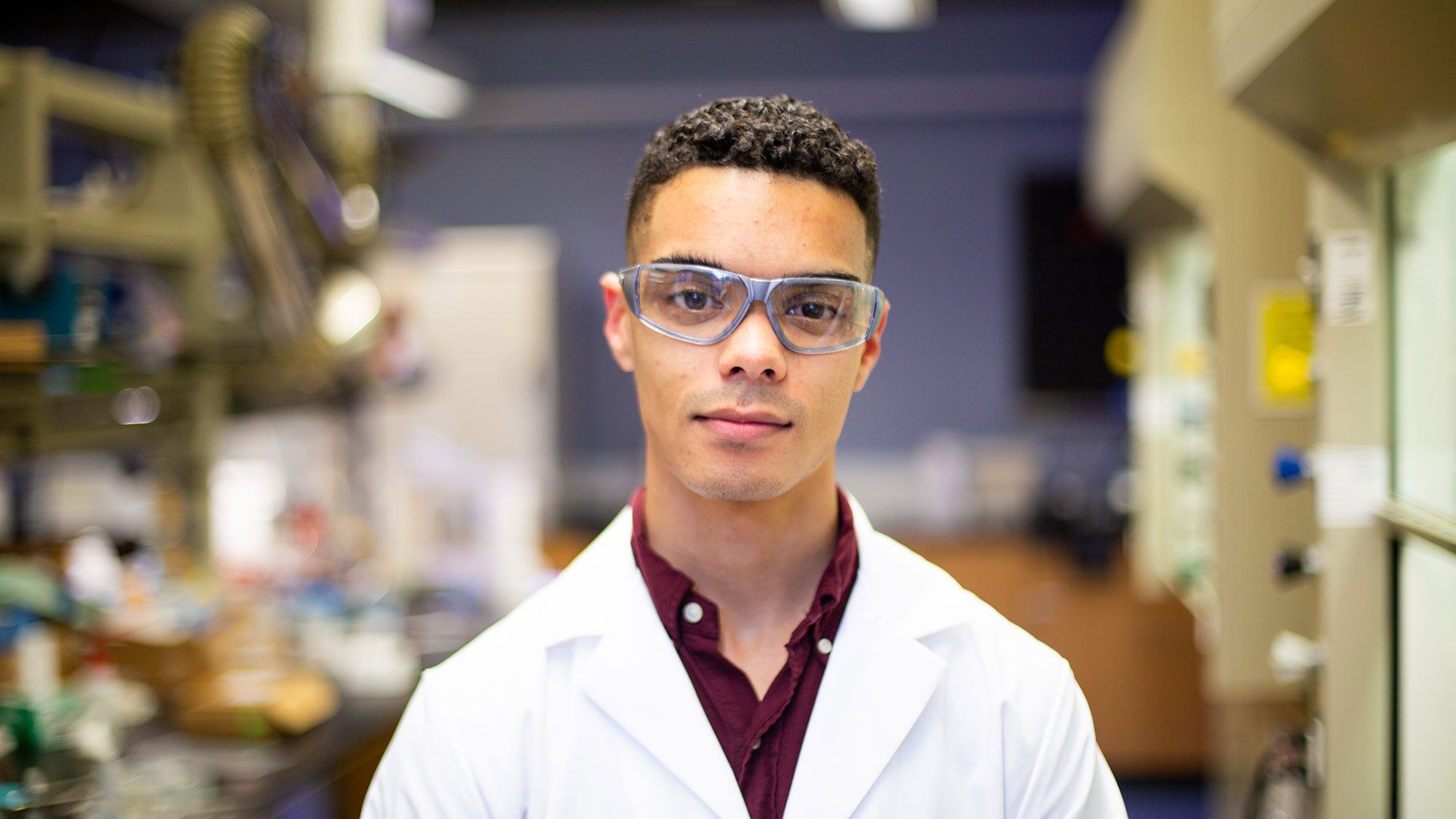 Orlando Stewart stands wearing a white lab coat and goggles in a laboratory.