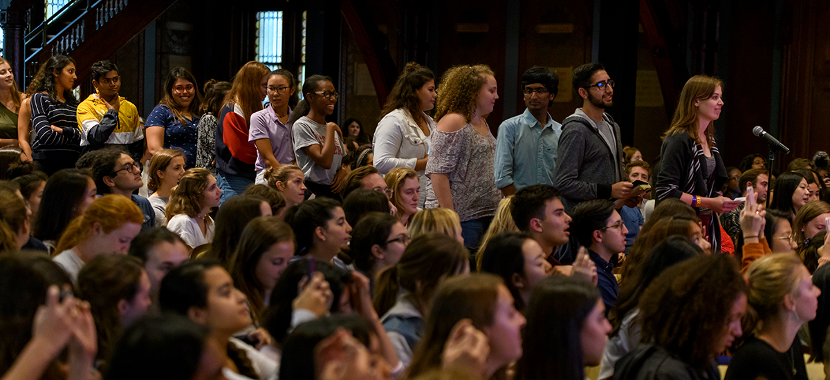 Students line up for the microphone in the aisle among a crowded audience.
