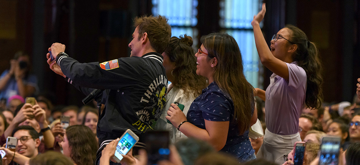 Bradley Cooper takes a selfie with a group of students standing in the aisle in Gaston Hall.