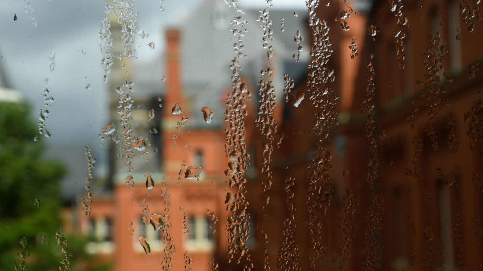 Rain trickles down a window with campus in the background