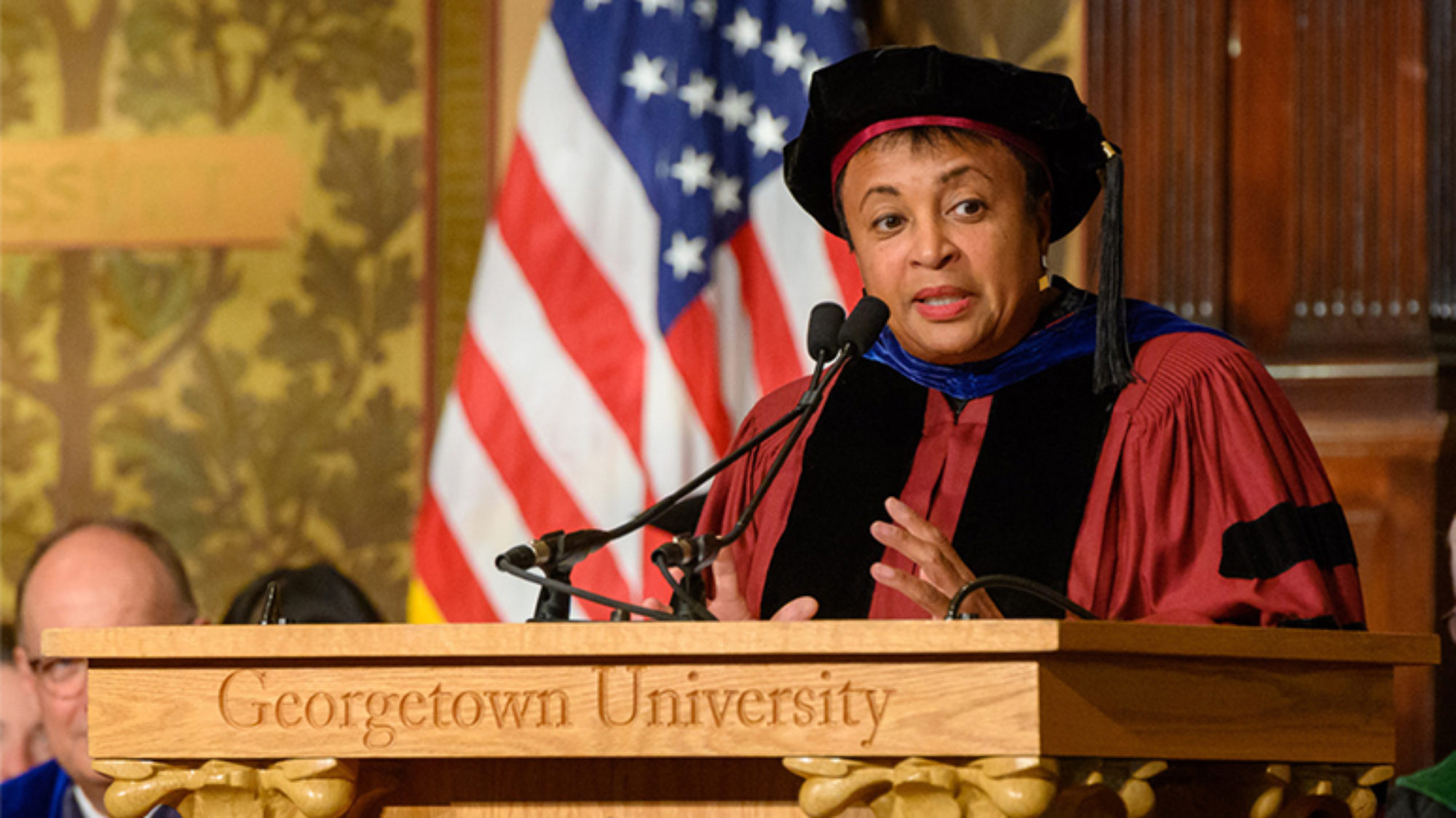 Carla Hayden at Georgetown University podium wearing cap and gown with American flag behind her