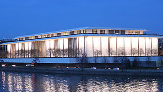 The Kennedy Centerr for the Performing Arts sits lit up at night with the Potomac River in the foreground.