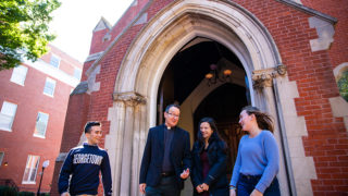 Rev. Mark Bosco, S.J. chats with students outside of Dahlgren Chapel.