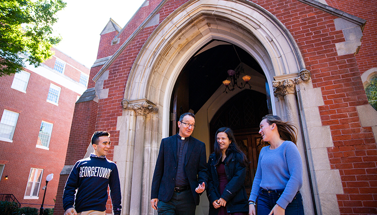 Rev. Mark Bosco, S.J. chats with students outside of Dahlgren Chapel.