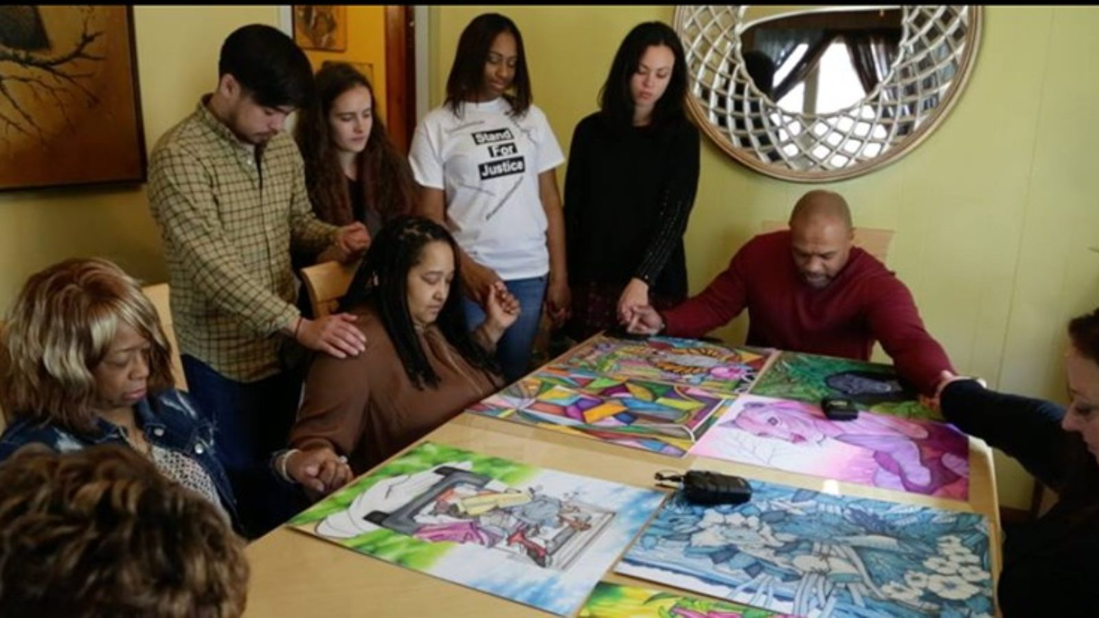 Valentino Dixon and family and Georgetown students hold hands and pray around table with Valentino Dixon's artwork