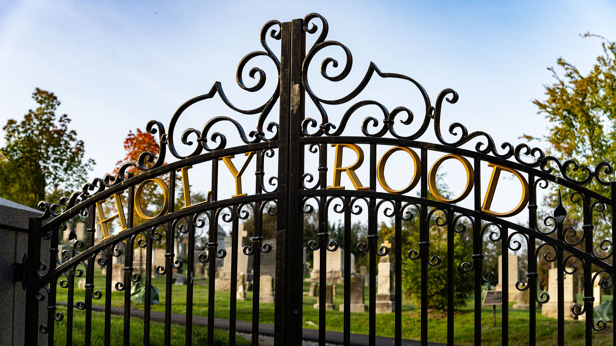 Holy Rood Cemetery's iron gate with tombstones in the background