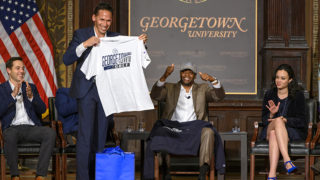 Marc Howard holds up Georgetown T-shirt as Valentino Dixon raises hands