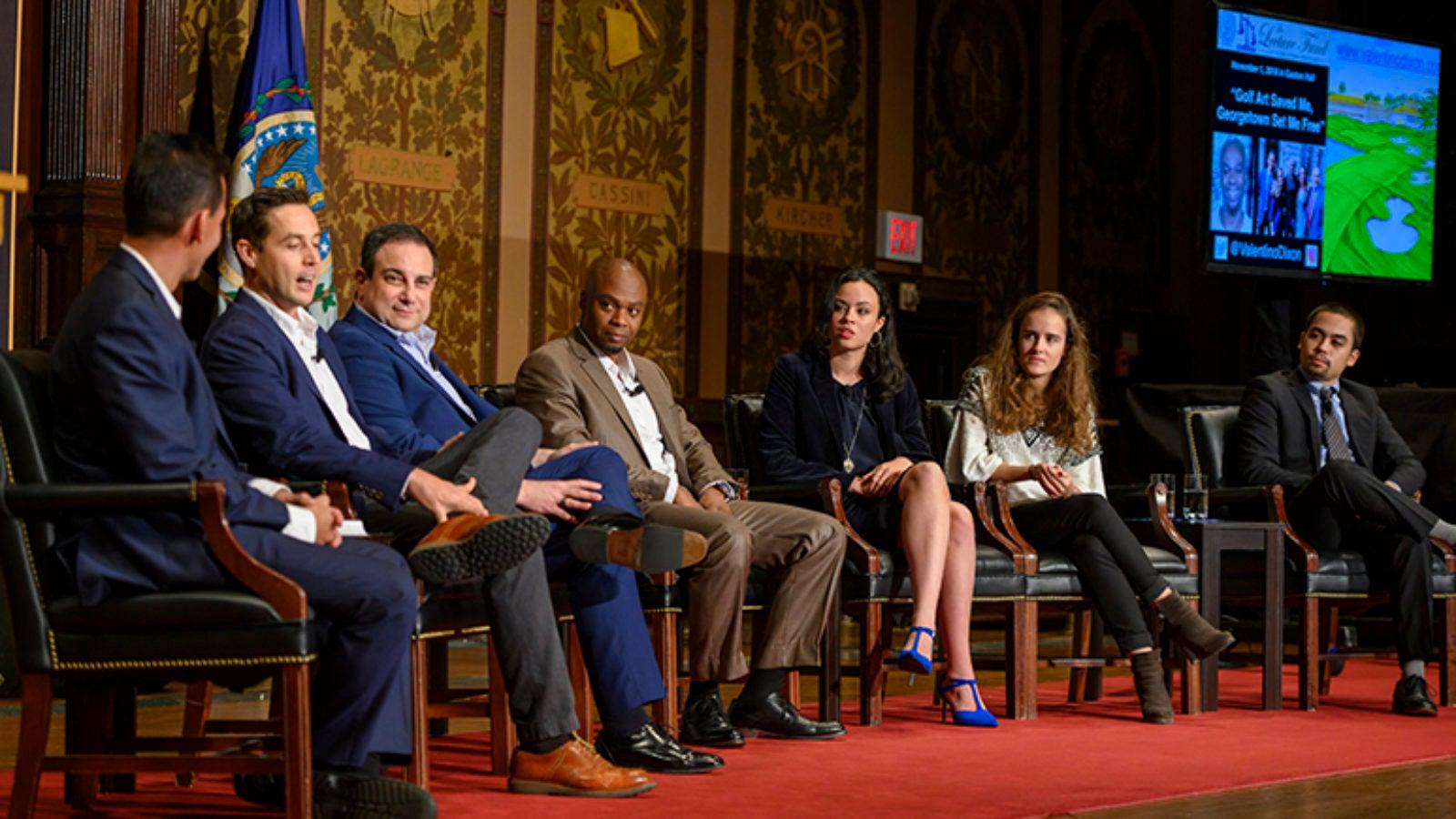 Marc Howard, Max Adler, Valentino Dixon, Isobella Goonetillake, Julie Fragonas and Naoya Johnson sitting onstage in Gaston Hall