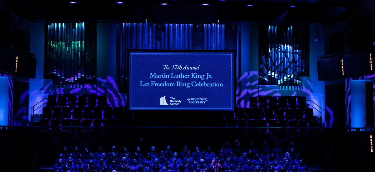 A dim blue-lit stage features a screen with The 17th Annual Martin Luther Ling Jr. Let Freedom Ring Celebrration