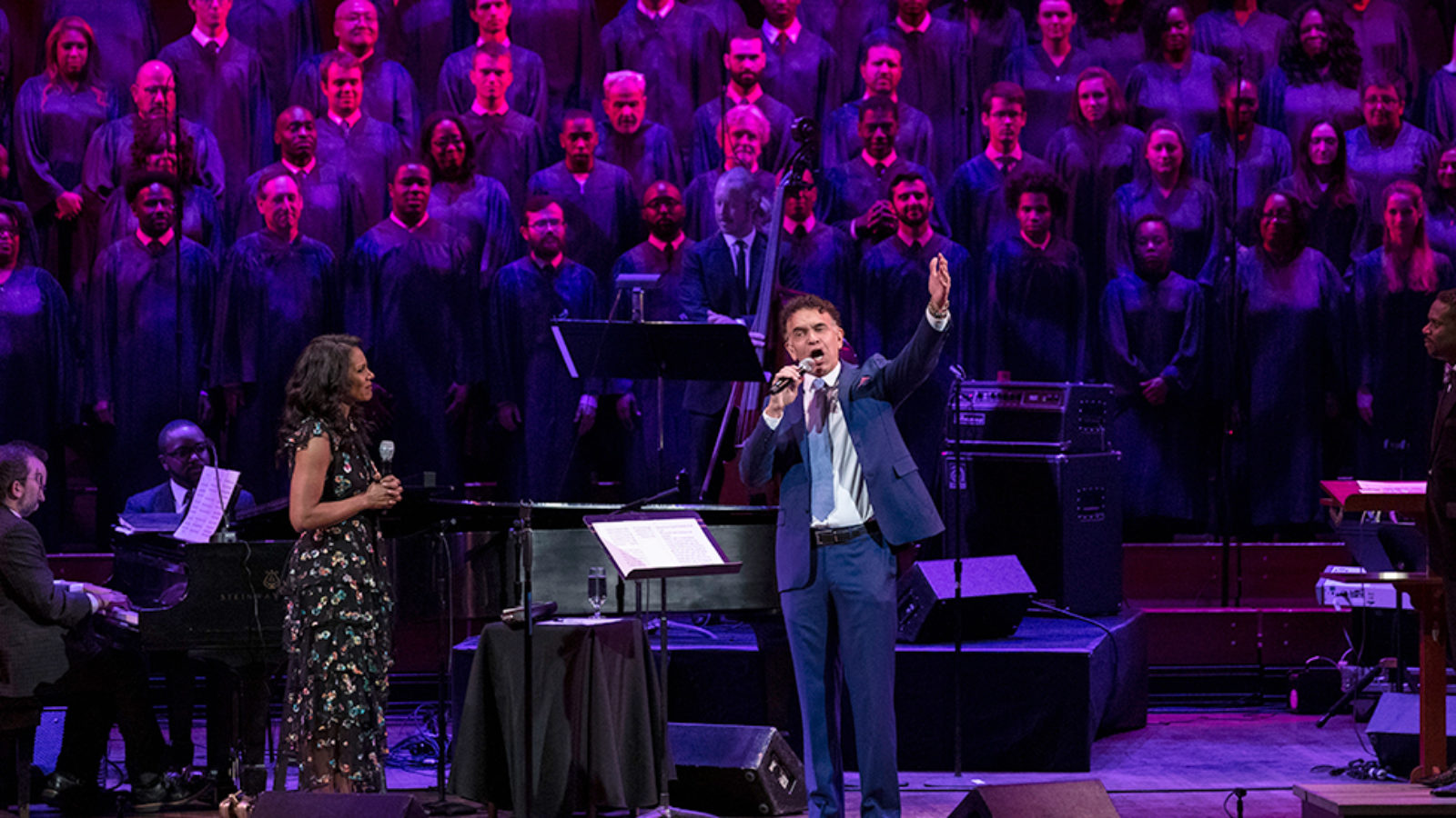 Audra McDonald looks on as Brian Stokes Mitchell sings with a choir singing on stage with him in the background.