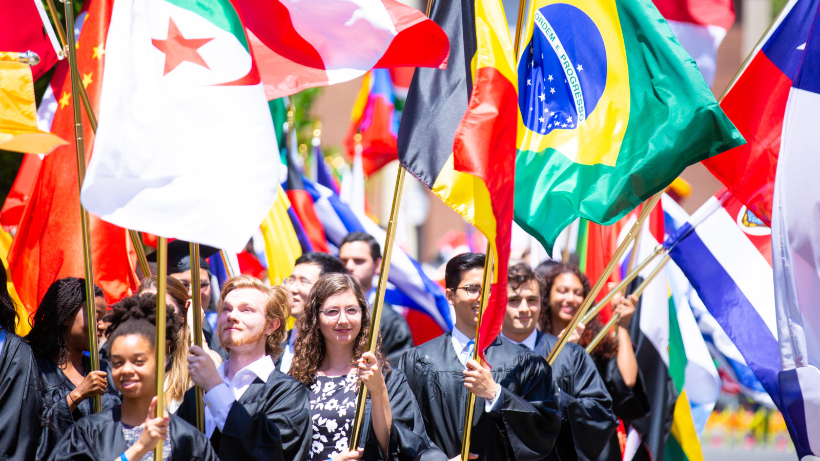Georgetown students in caps and gowns holding large flags from different countries