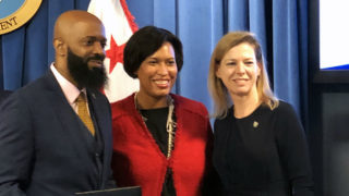 Milford Washington stands to the left of DC Mayor Muriel Bowser and Kelly Otter stands to the right.