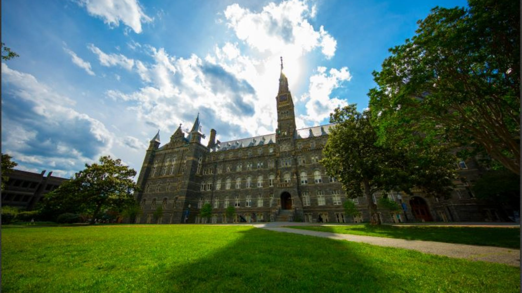 Healy Hall with green lawn and blue sky and fluffy clouds behind it