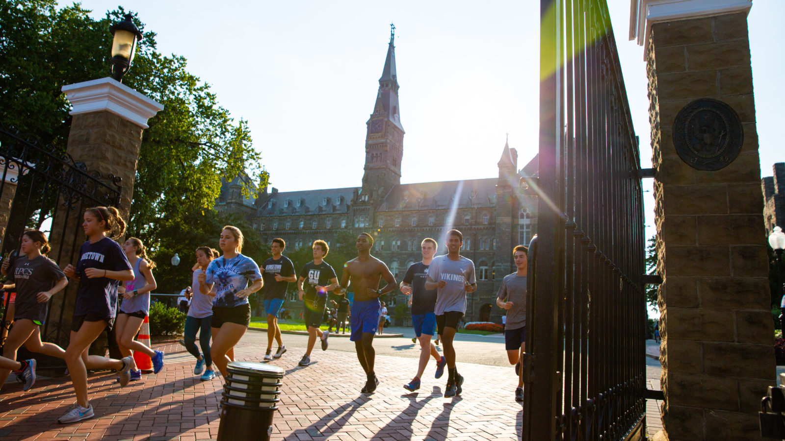 Runners run through Georgetown's front gates.