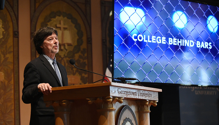 Ken Burns at podium with screen behind him reading College Behind Bars