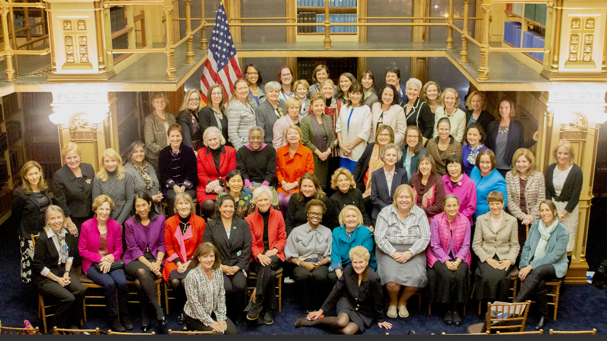 A group of about 60 women sit and stand for a photo together in Riggs Library.