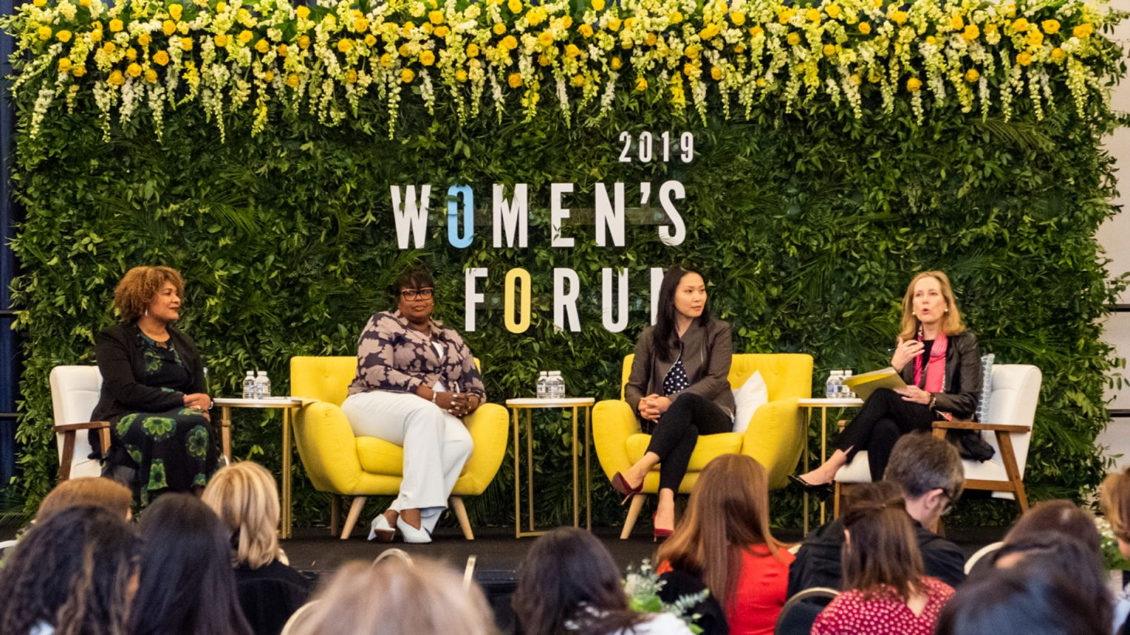 Fatima Goss Graves, Juliette Pryor, Nicolina O'Rorke and Hillary Sale talk on stage with 2019 Women's Forum in background.