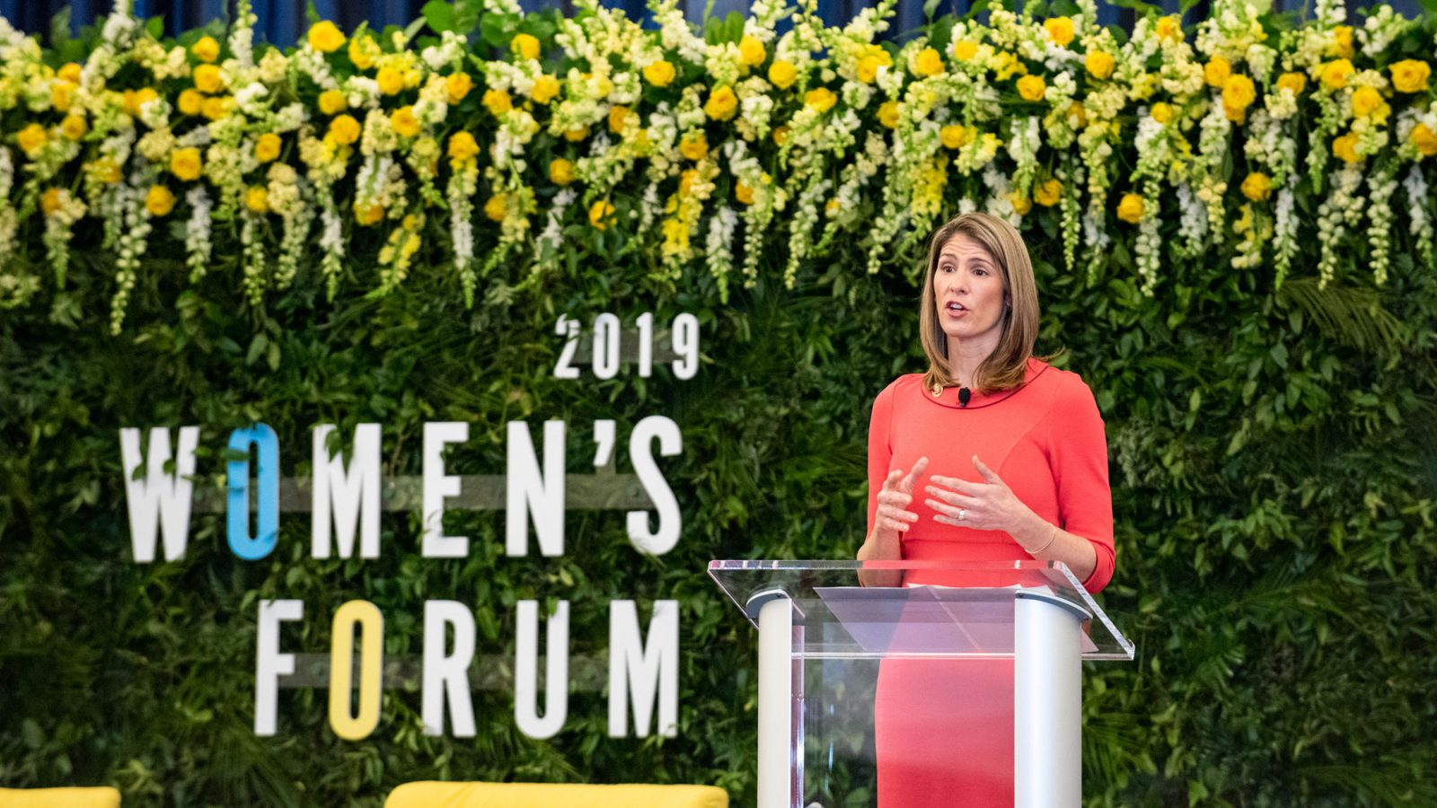 Lori Trahan speaks on stage standing at the microphone with 2019 Women's Forum signage in the background.