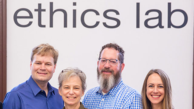 Nitin Vaidya, Ray Essick, Maggie Little, Mark Maloof, Elizabeth Edenberg and Jonathan Healy standing in front of the Ethics Lab sign.