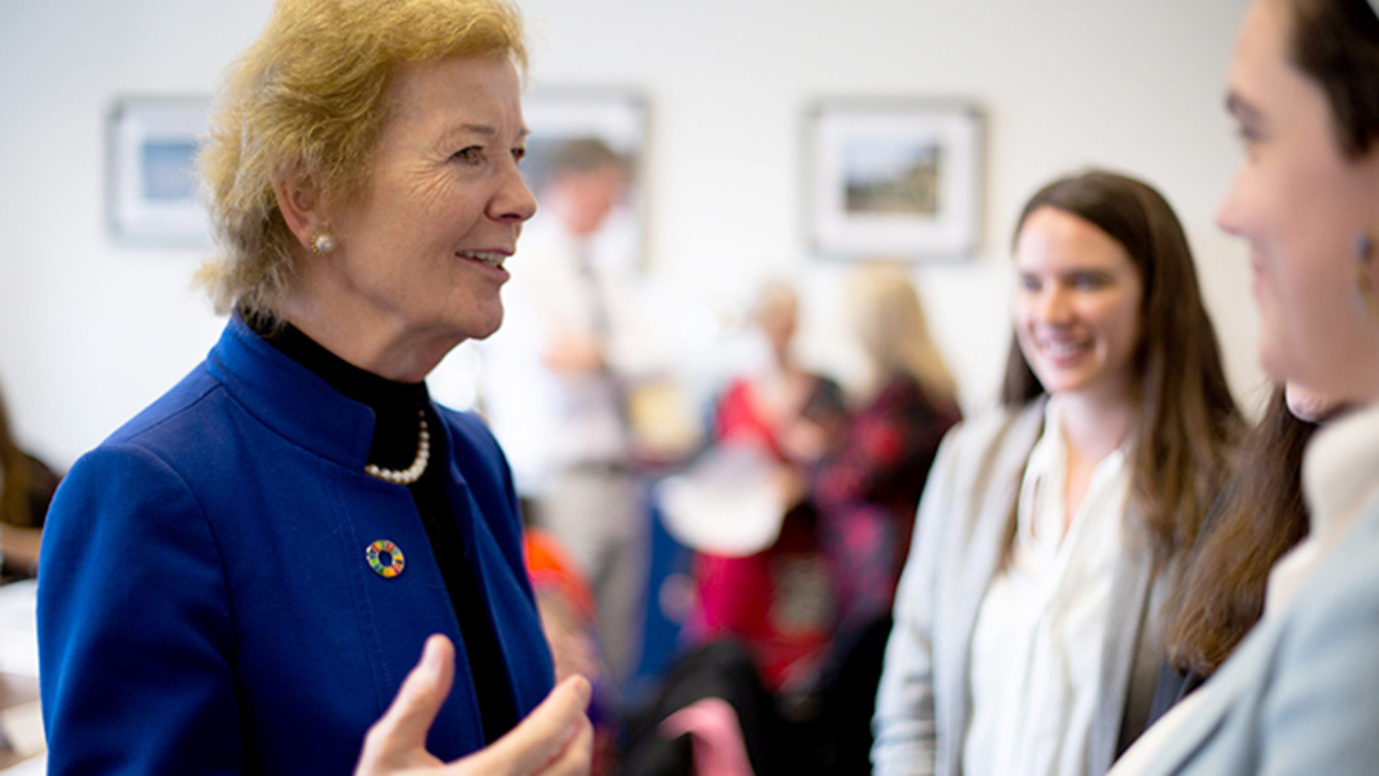 Former Ireland President Mary Robinson stands and talks with a few students with more students in the background