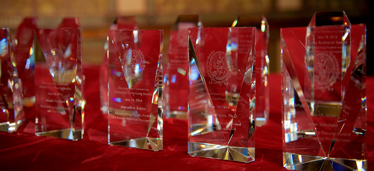 A grouping of glass awards sit on a table covered in red velvet