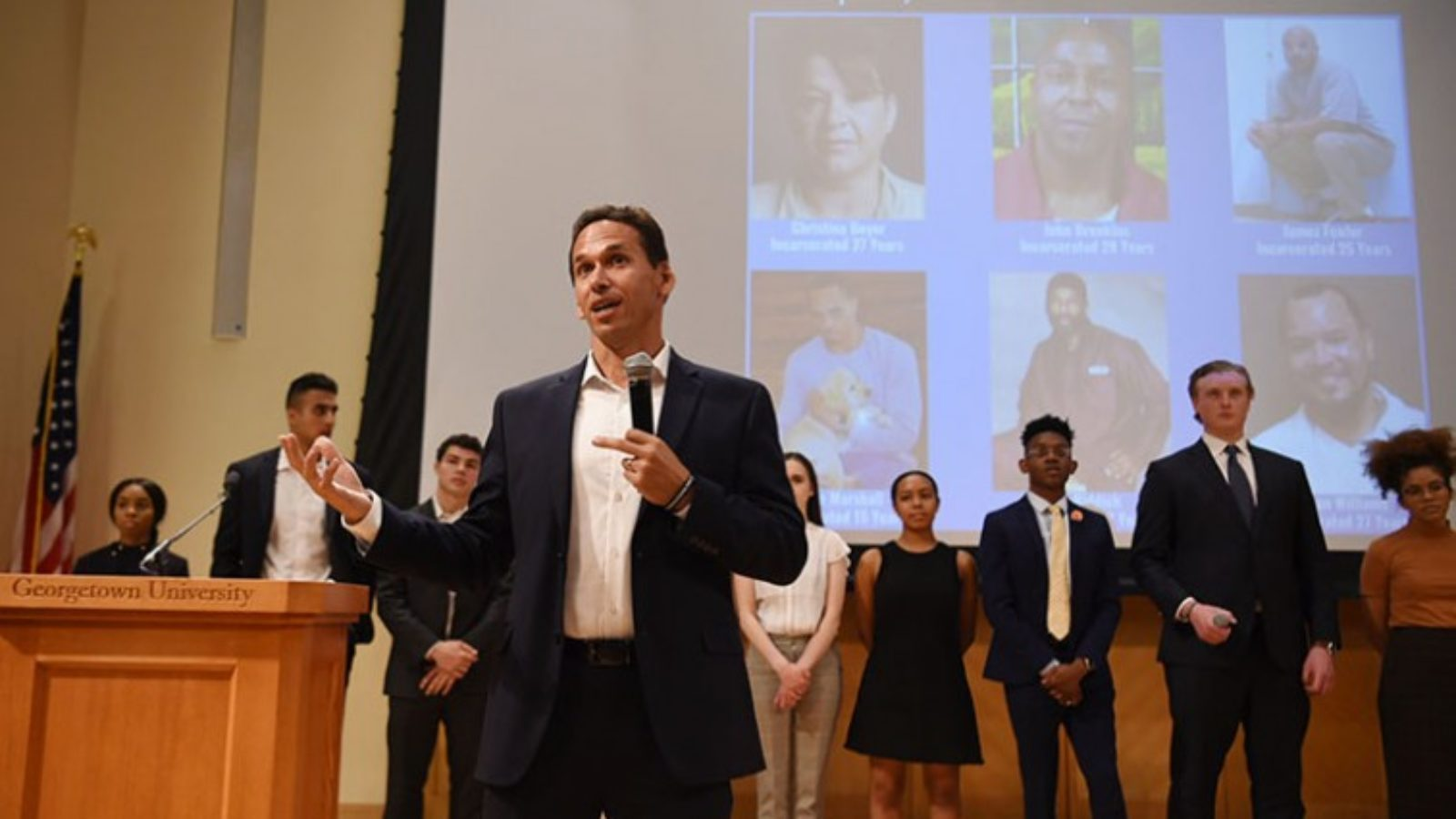 Marc Howard standing with microphone in front of students and video screen of six incarcerated individuals
