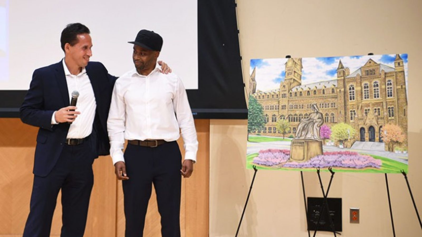 Marc Howard and Valentino Dixon on a stage with Dixon's artwork