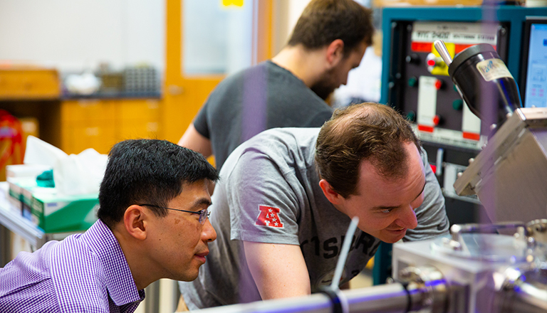 Georgetown physics professor Kai Liu and two graduate students work with equipment in a lab.
