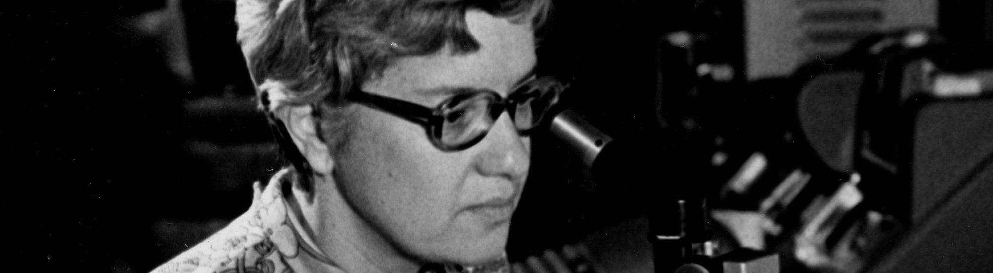 Vera Rubin looks into a microscope