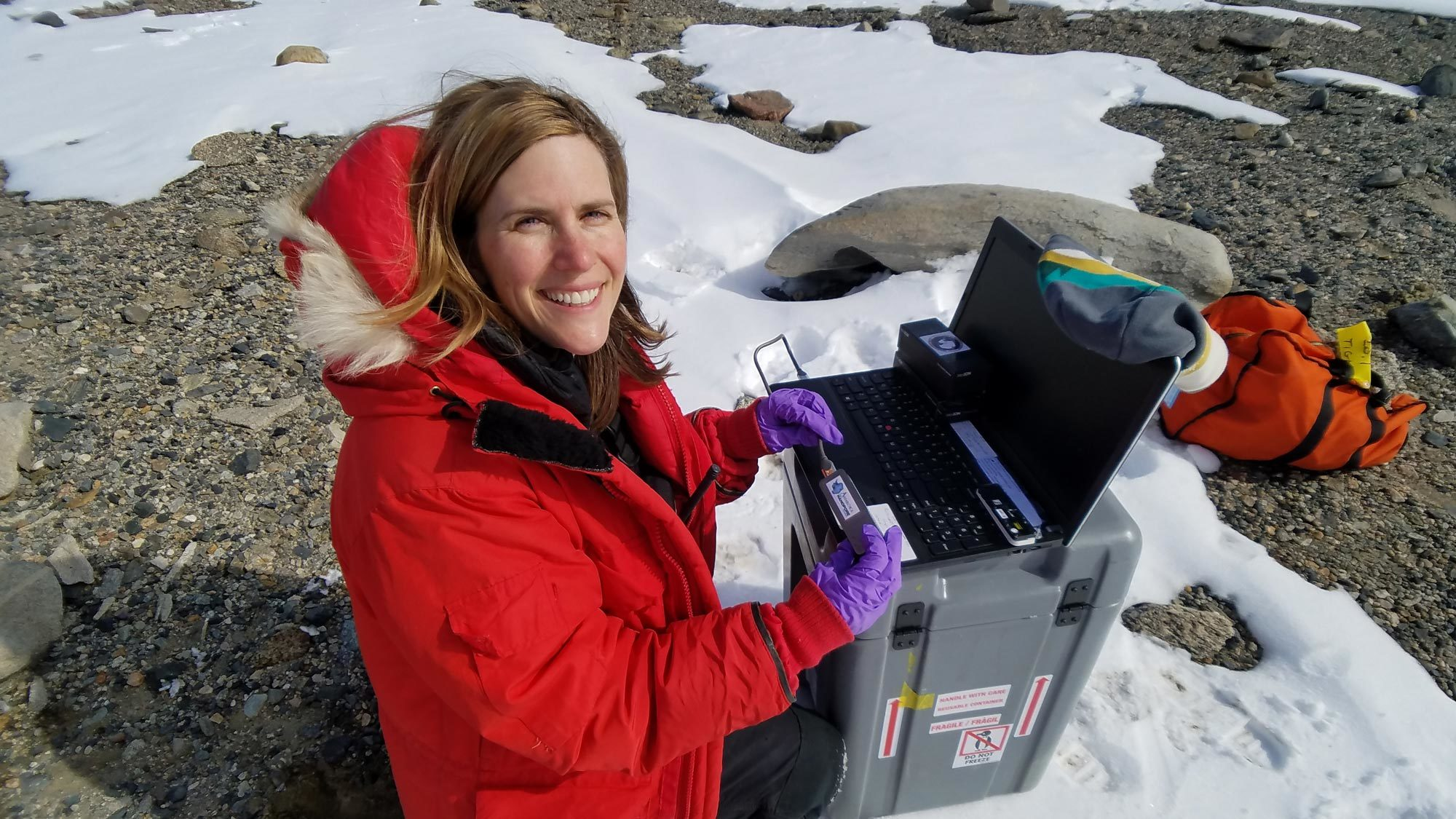 Sarah Johnson collects samples while sitting on a snow-covered ground in Antarctica.