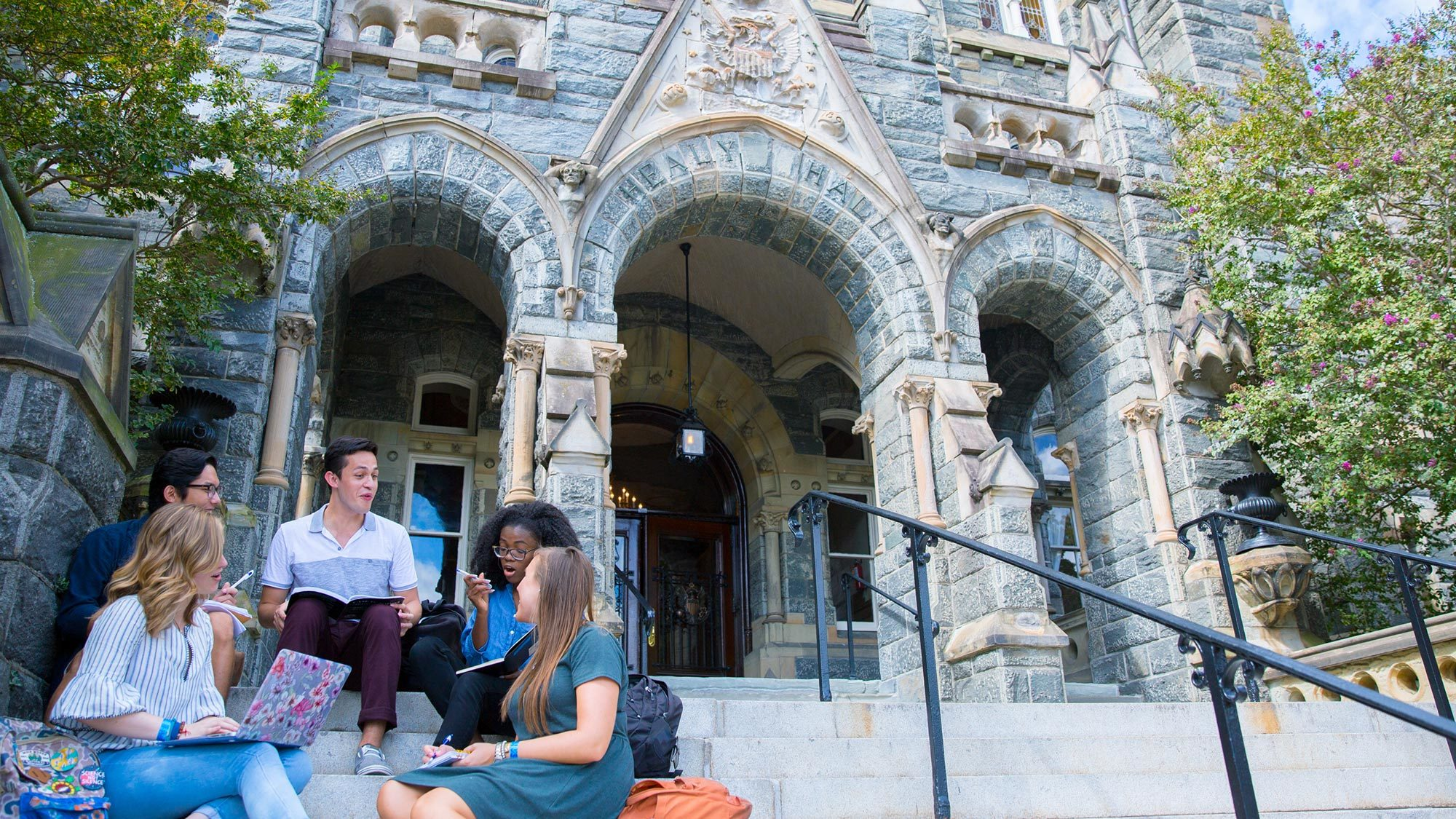 Students sit on the steps of Healy Hall.